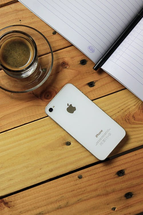 Silver Iphone 6 Beside Clear Glass Mug on Brown Wooden Table