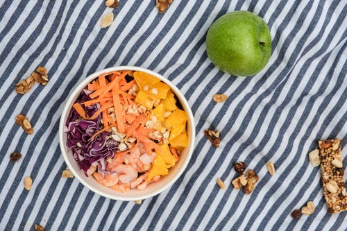 Top view of fresh poke bowl near green apple and nuts on surface