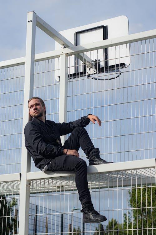 Stylish man sitting near basketball court