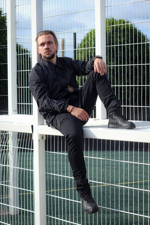 Handsome man sitting on fence at daylight