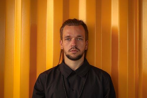 Stylish man against yellow wall at daylight