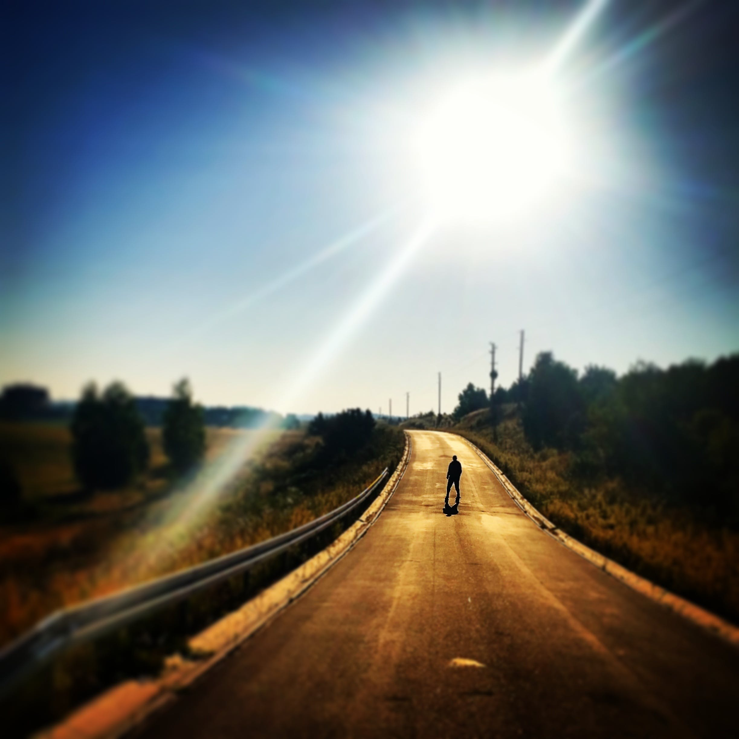 Person Standing on Blacktop Road Under Blue Sky During Daytime