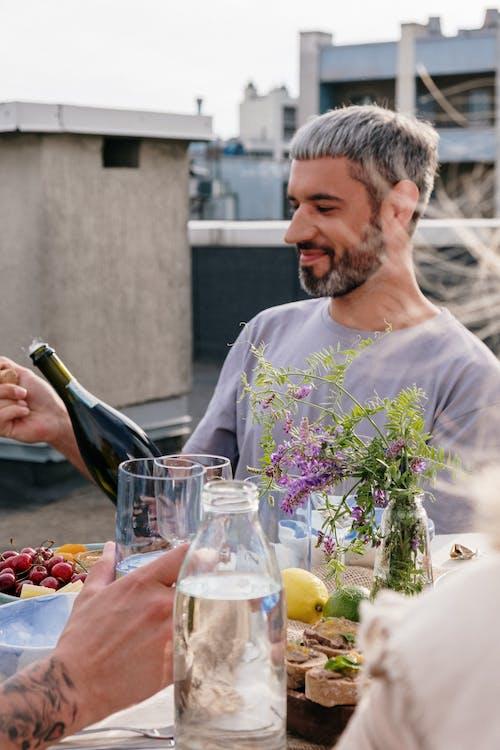 Man in White Crew Neck T-shirt Holding Wine Bottle