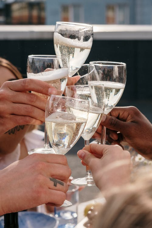 People Holding Clear Wine Glasses