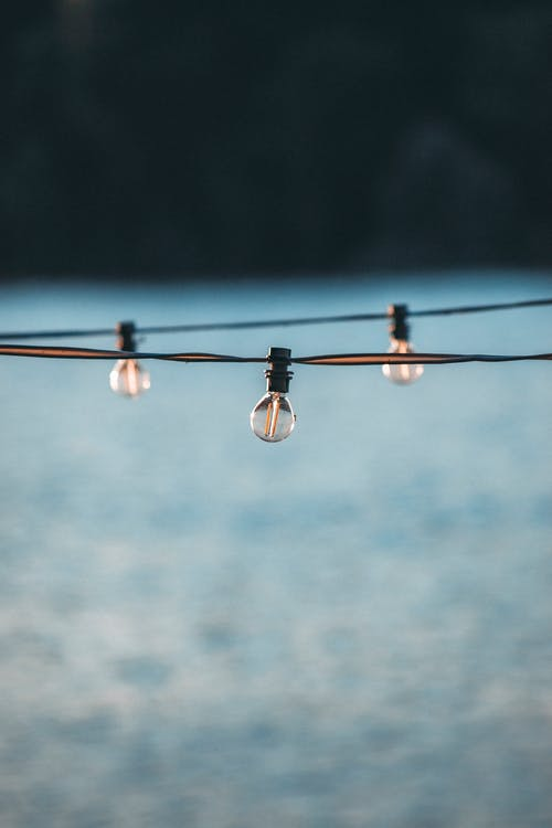 Small bulbs on cable above gray blurred surface