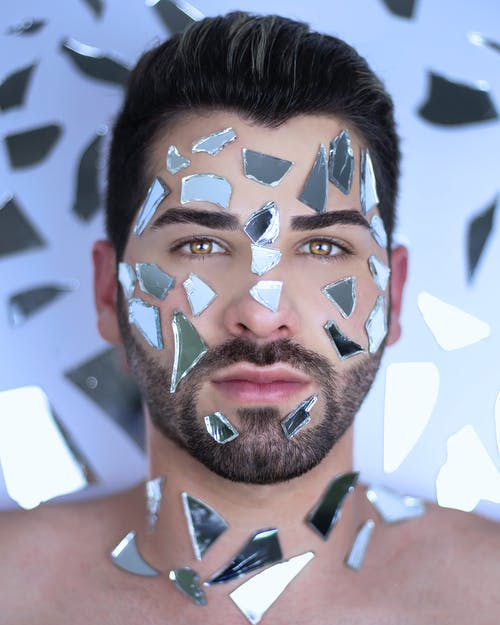 Bearded man with mirror pieces on face