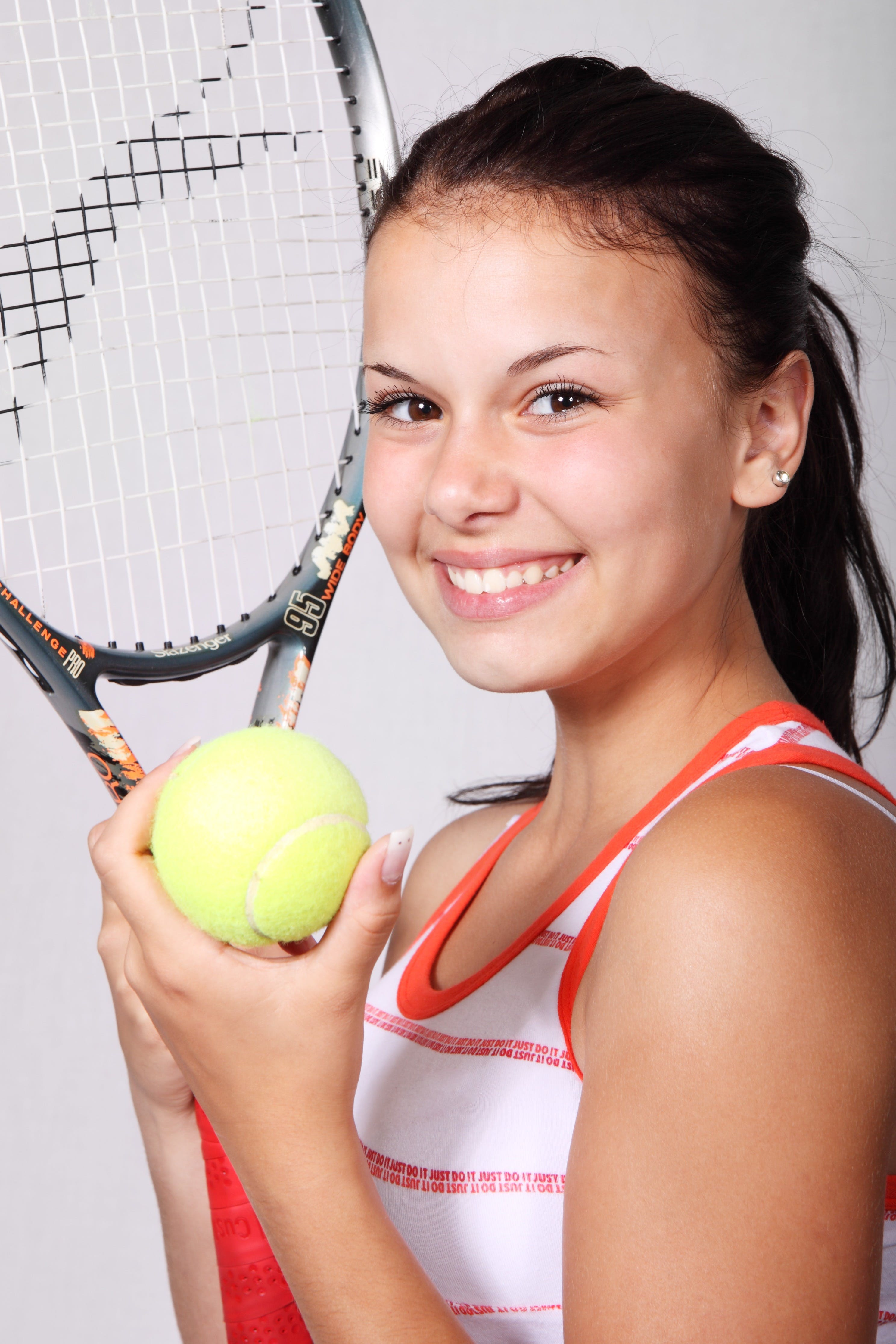 Girl in White and Orange Stripe Tank Top Holding Black Tennis Racket