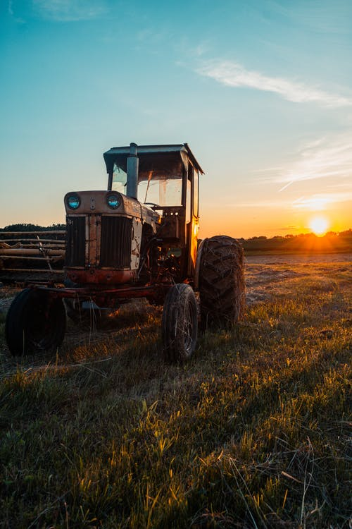 Tractor On Green Grass Field During Sunset