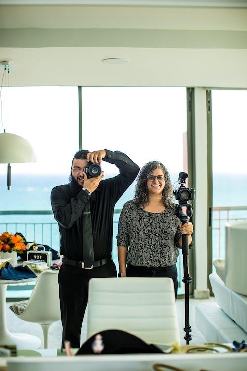 Cheerful photographers taking photo on photo camera in modern interior
