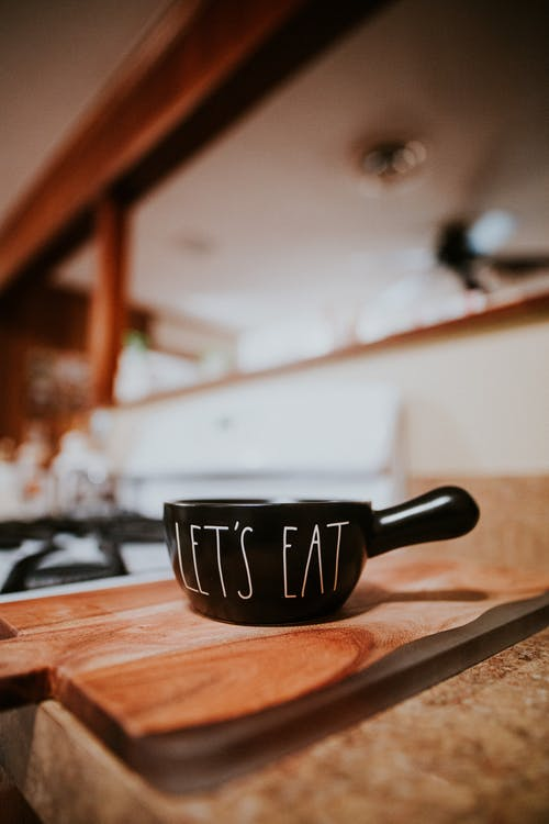 Black bowl with handle with inscription Lets Eat