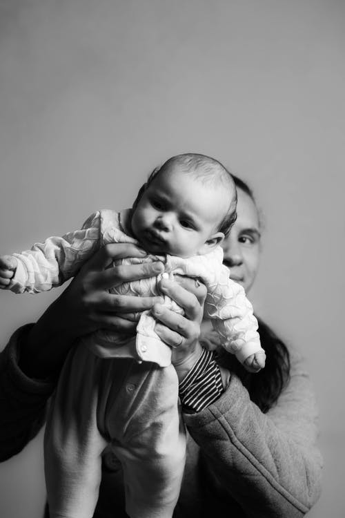 Grayscale Photo Of Man Carrying Baby