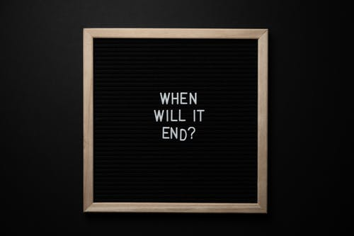 Chalkboard with When Will It End inscription on black background