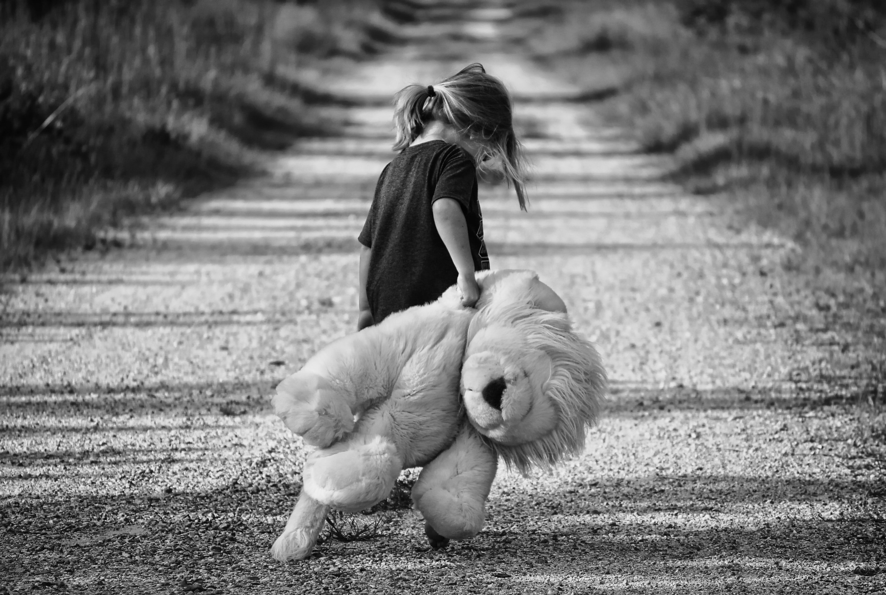 Grayscale photography of girl holding plush toy · free stock photo