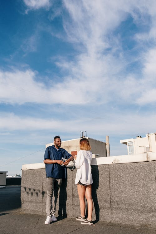 Man and Woman Standing on Top of Building