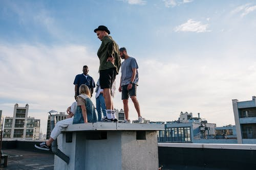 Man in Gray T-shirt and Black Shorts Standing on Gray Concrete Dock