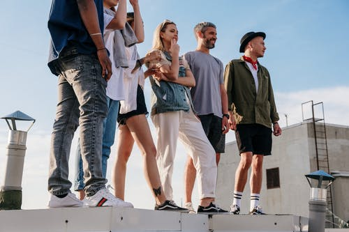 Group of People Standing on White Concrete Wall