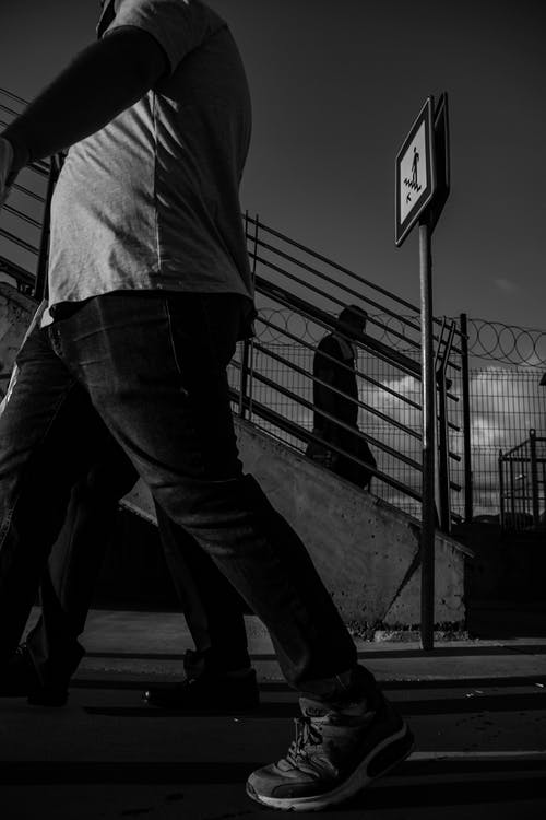 Grayscale Photo of Man in White Shirt and Black Pants Standing on Road