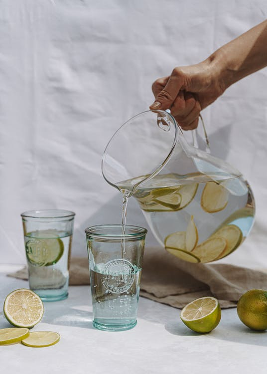 Crop person holding jug and pouring fresh lemonade into glass on white textile background