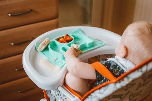 Baby in a High Chair Eating Food