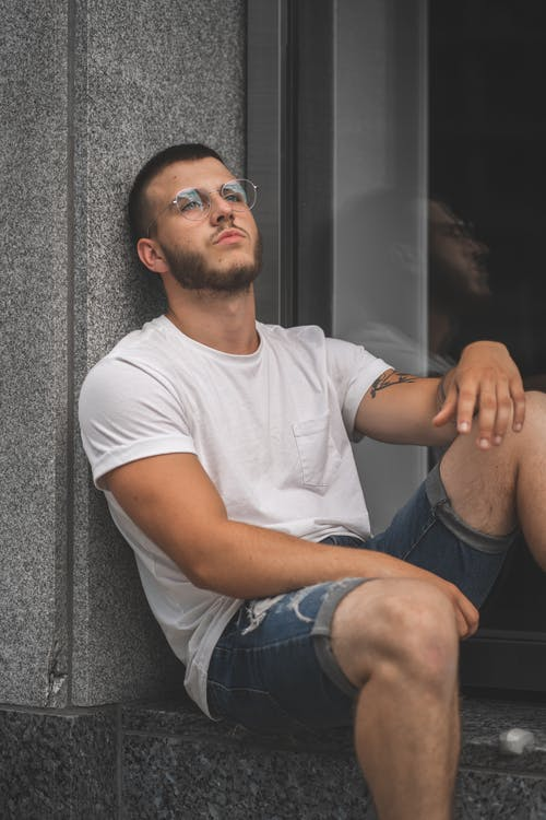 Man in White Crew Neck T-shirt and Blue Denim Shorts Sitting on Black Chair