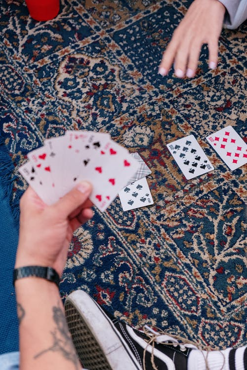 Person Holding Playing Cards on Brown and Black Floral Area Rug