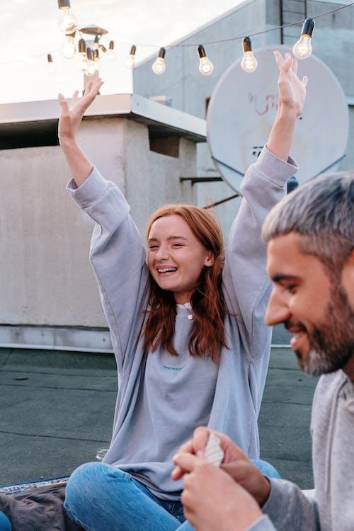 Foto stok gratis angkat tangan, atap, berambut merah