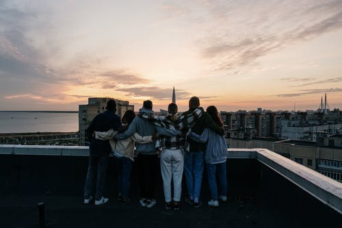 Group of People Standing on Top of Building during Sunset