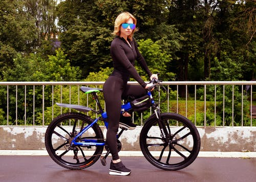 Confident young woman preparing for bicycle ride on sunny day