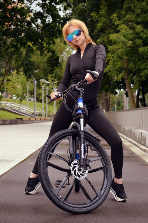Stylish young lady sitting on modern bicycle in city park
