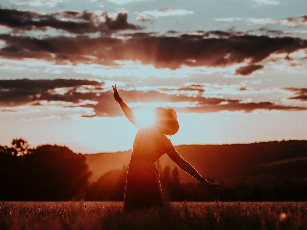 Silhouette of woman dancing in field
