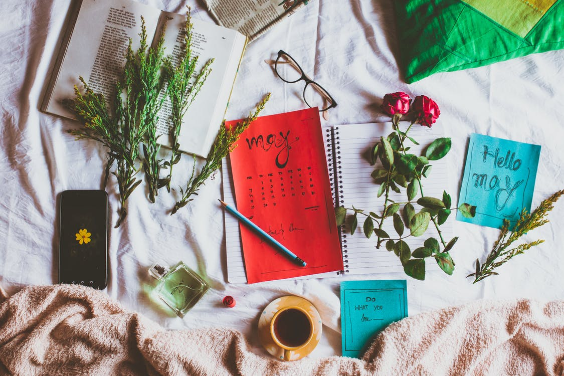 From above of colorful calendar near plant sprigs and mug of hot drink on creased fabric with perfume and smartphone