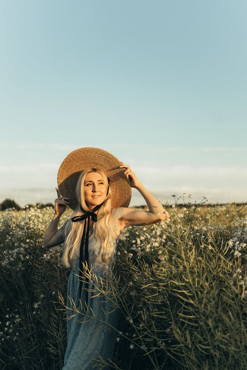 Woman in White Dress and a Sun Hat Standing on Flower Field