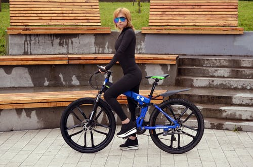 Side view of stylish slender female wearing black clothes standing on pedal of modern bicycle near wooden benches in park