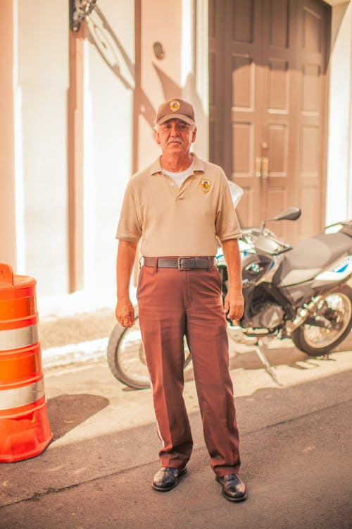 Full body calm elderly male in stylish brown trousers and cap standing on sunny street near motorbike and looking at camera