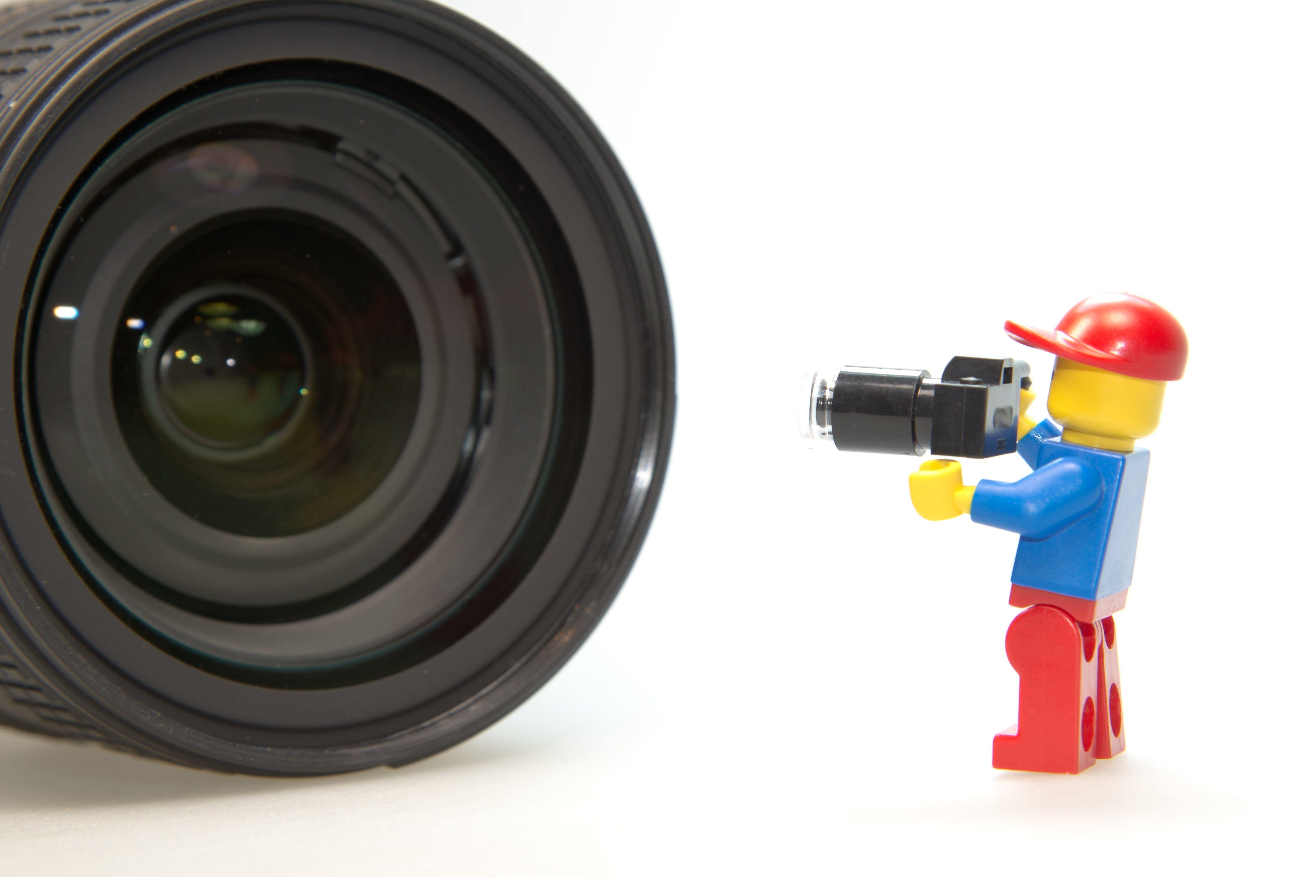 Blue and Red Lego Toy Taking Picture on Black Camera Lens