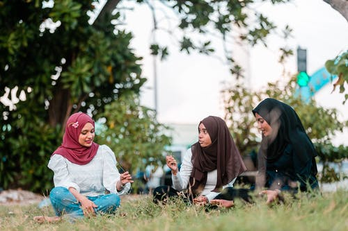 Positive Muslim women resting on grassy lawn