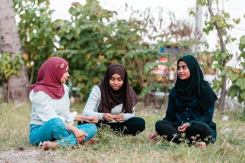 Muslim women sitting on grass in park and talking