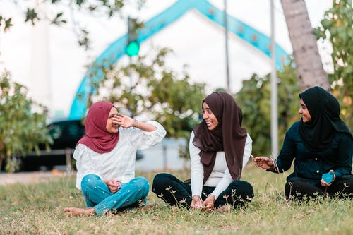 Young Muslim women laughing while resting on grass