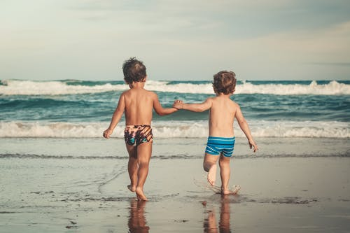 Back view of anonymous shirtless little brothers holding hands and walking on wet sandy beach towards waving ocean during summer holidays
