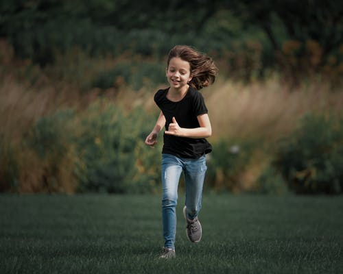 Cheerful child running in field in summer