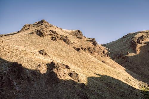 Rough mountains illuminated by sunlight under sky