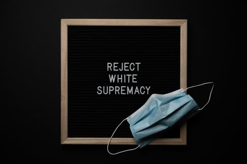 Top view of disposable mask on chalkboard with Reject White Supremacy inscription on black background