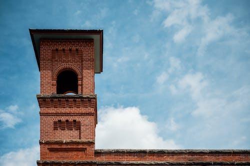 Campanile of old brick church under cloudy sky