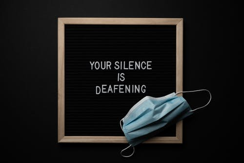Overhead view of respiratory mask on chalkboard with Your Silence Is Deafening title during quarantine period