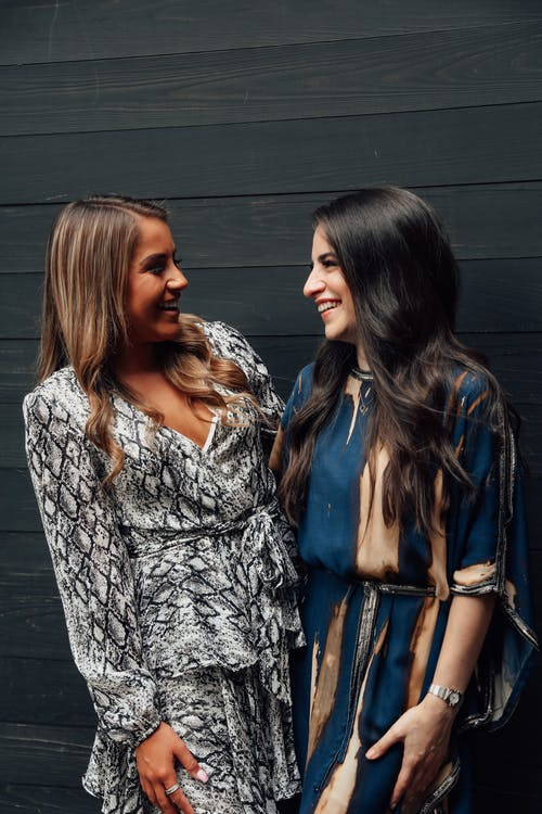 Cheerful young multiethnic female friends looking at each other with bright toothy smile next to black wooden wall in daytime