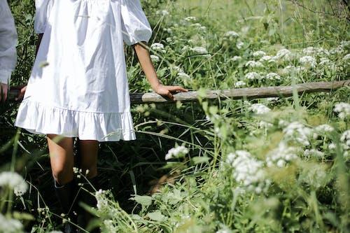 Girl in White Dress Standing on Brown Wooden Bridge