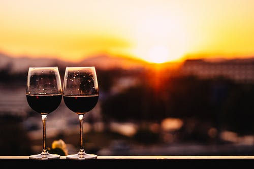 Wineglasses with red wine placed on wooden handrail against bright sun at romantic sundown