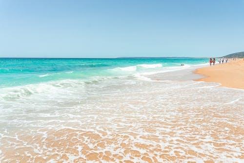 Foamy waves of turquoise sea rolling near sandy wet shore while travelers enjoying amazing summer holidays