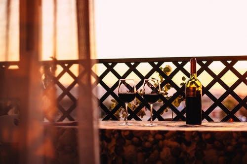 Red wine in wineglasses and placed near bottle on table in cozy outdoor veranda