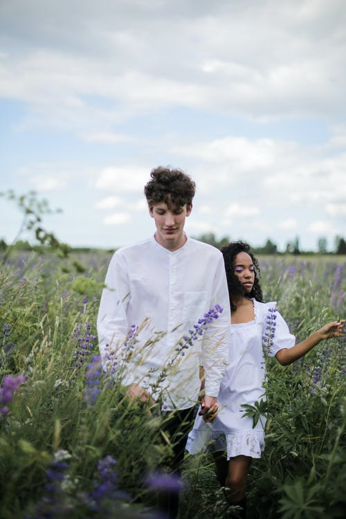 Man in White Dress Shirt Standing Beside Woman in White Dress on Purple Flower Field during